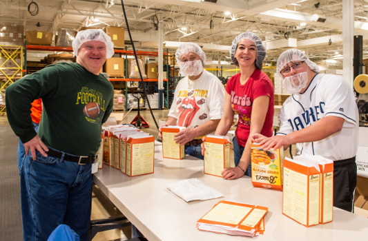 Production workers with down syndrome and other barriers to employment folding cartons.