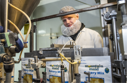TVS employee working packaging production, machine operator, bakery mix, mountain maid.