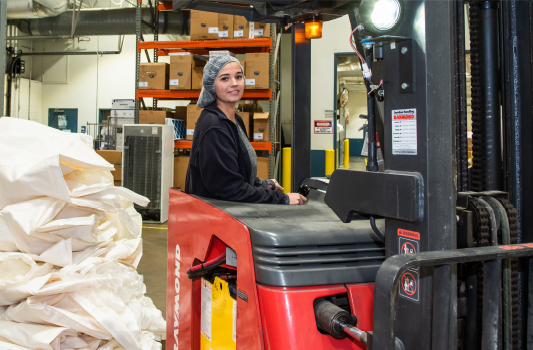 Female TVS forklift driver moving products and pallets around the manufacturing floor.