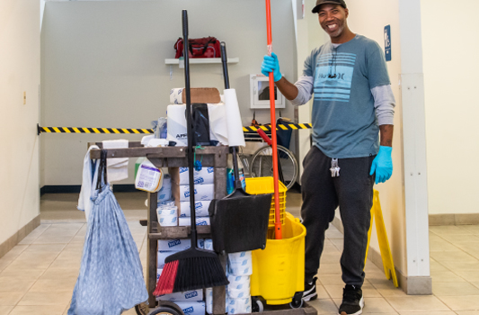 Housekeeping employee keeps the facility clean by cleaning restrooms and collecting trash.