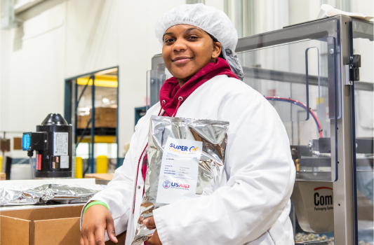 African American TVS Production line employee wearing lab coat holding Super Cereal Plus bag.