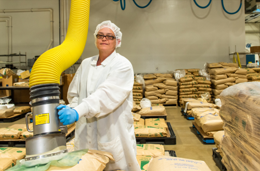 TVS production employee using a vacuum lift system for blending Mountain Maid baking mix